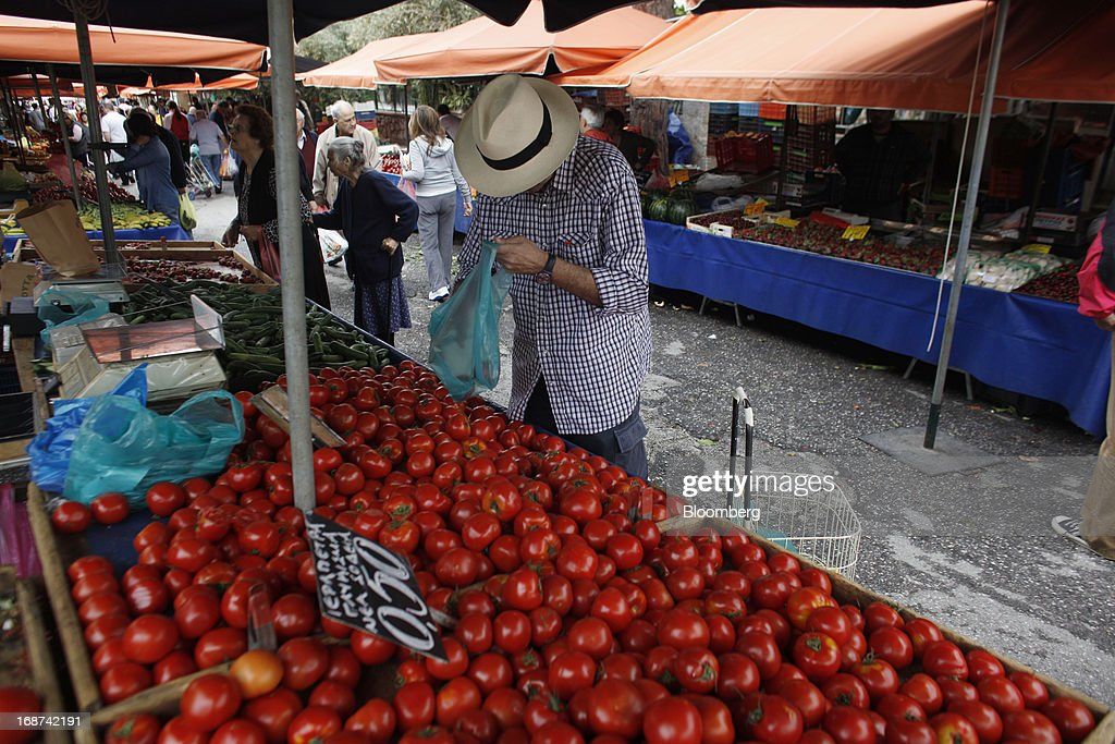 A customer selects fresh tomatoes sold at an open air market in the Ilioupolis district of Athens, Greece, on Tuesday, May 14, 2013. Greek Prime Minister Antonis Samaras said the country can beat the targets set under its 240 billion-euro ($311 billion) International Monetary Fund and euro area bailout program and return to bond markets in the first half of next year. Photographer: Kostas Tsironis/Bloomberg via Getty Images