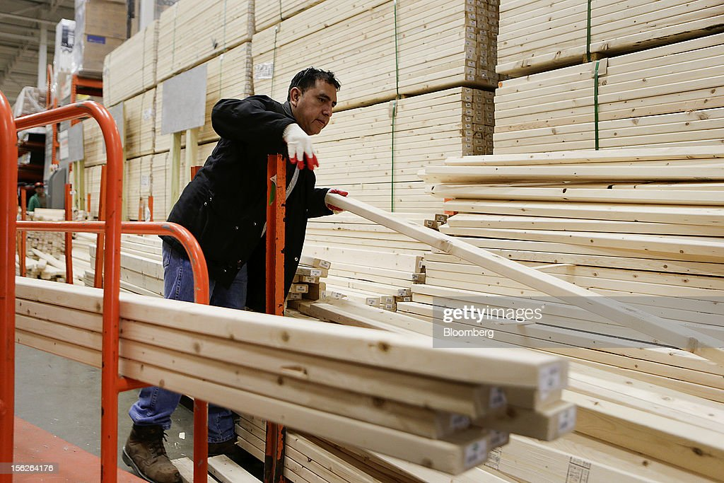 A customer selects lumber at a Home Depot Inc. store in Washington, D.C., U.S., on Monday, Nov. 12, 2012. The Home Depot Inc. is scheduled to release earnings data on Nov. 13. Photographer: Andrew Harrer/Bloomberg via Getty Images