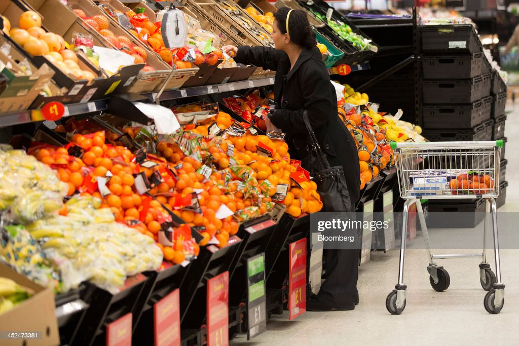 A customer selects oranges form the fruit and vegetable display aisle inside an Asda supermarket in Wembley, London, U.K., on Friday, Nov. 29, 2013. Britons queued outside Asda supermarkets this morning and charged into stores when doors opened at 8 a.m. as the U.K. grocery chain took on the Black Friday mantle from U.S. owner Wal-Mart Stores Inc. Photographer: Simon Dawson/Bloomberg via Getty Images