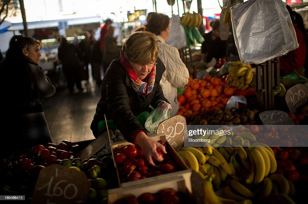 A customer selects tomatoes from a fruit and vegetable stall in the weekly market in Figueres, Spain, on Thursday, Jan. 31, 2013. Spain's recession deepened more than economists forecast in the fourth quarter as the government's struggle to rein in the euro region's second-largest budget deficit weighed on domestic demand. Photographer: David Ramos/Bloomberg via Getty Images
