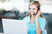 A customer service agent smiles in front of her laptop