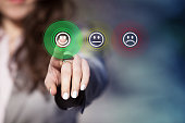 Businesswoman pressing smiley face emoticon on virtual touch screen. Customer service evaluation concept.