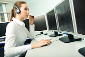 Photo of pretty consultant wearing headset and sitting in front of computer display while consulting client   Note to inspector: the image is pre-Sept 1 2009