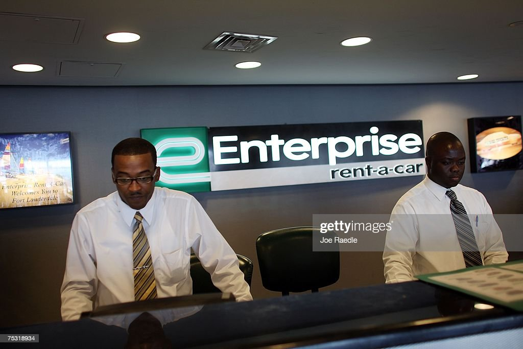 Customer service representatives Oneal West (L) and Marmontel Michel wait on customers at Enterprise rent-a-car at the Fort Lauderdale/Hollywood International airport July 10, 2007 in Fort Lauderdale, Florida. Pending regulatory approval, expected in the next month, Enterprise will buy National and Alamo rental car companies. Enterprise would make an instant jump from about 8% of the airport car rental market market to more than 27% just behind Hertz's 28.5%.