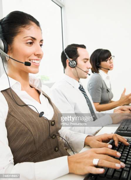 Customer service representatives wearing headsets using computers