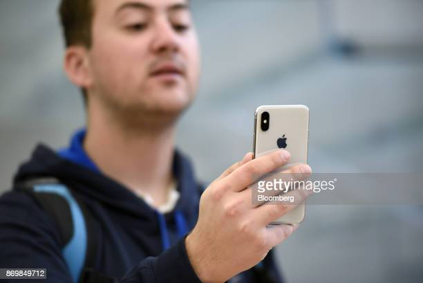 A customer sets up facial recognition on an Apple Inc iPhone X smartphone during the sales launch at a store in San Francisco California US on Friday...