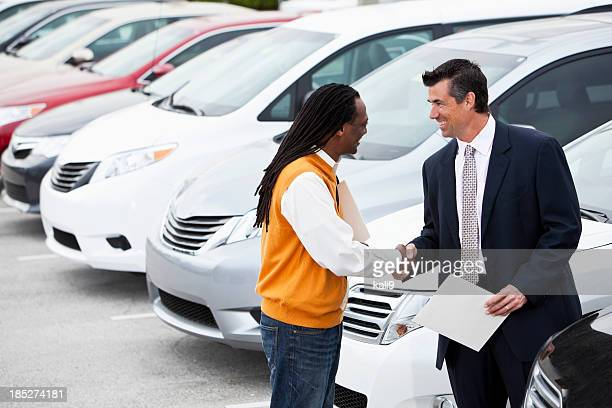Customer shaking hands with car salesman