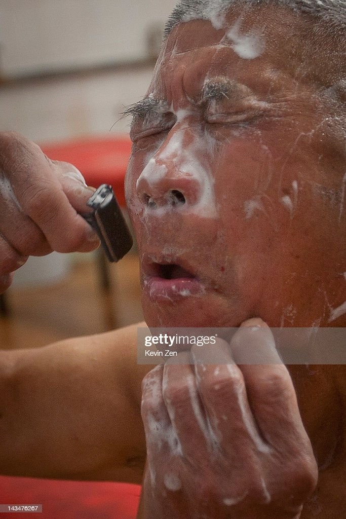 A customer shaves after bathing at Shuangxing Tang Bathhouse on December 8, 2011 in Beijing, China. The Shuangxing Tang Bathhouse is the last remaining public bathhouse in Beijing and faces demolition as the area undergoes development. Opened on 1916, the bathhouse provides its patrons with a culture that is dying out, offering traditional treatments and massages it stands as a relic of the old Beijing, but with ever-decreasing water resources its future remains uncertain.