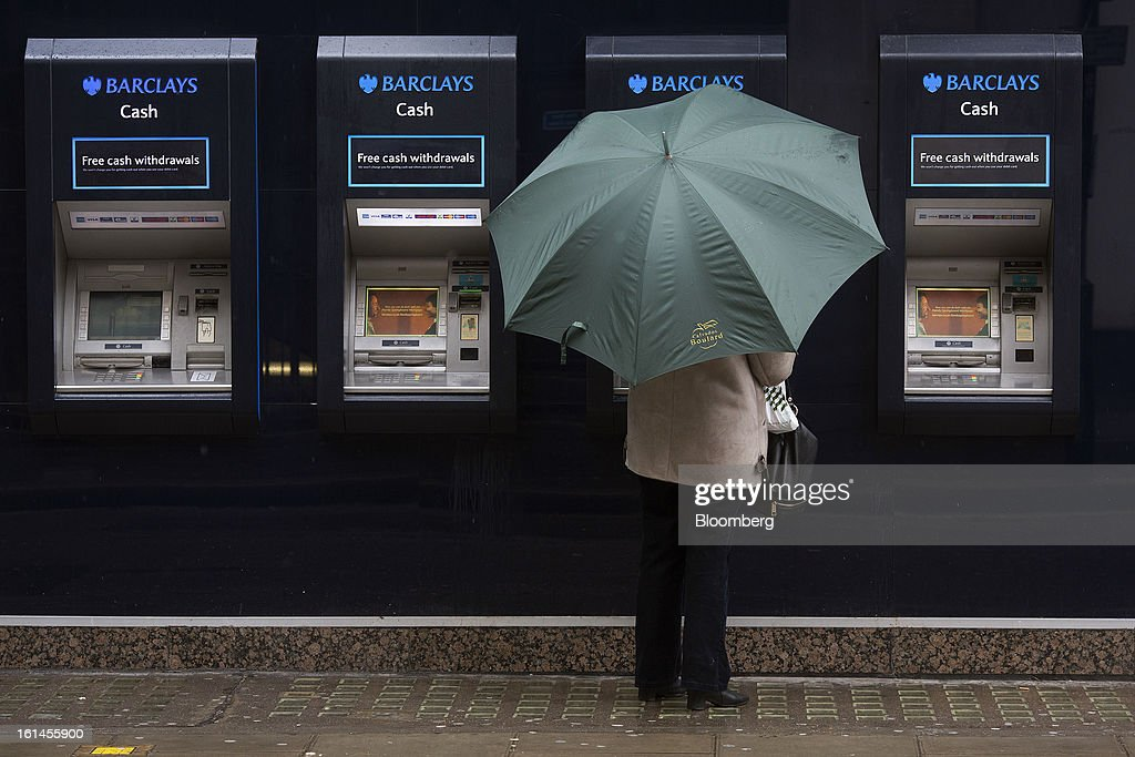 A customer shelters beneath an umbrella as she uses an automated teller machine (ATM) outside a Barclays Plc bank branch in London, U.K., on Monday, Feb. 11, 2013. Barclays Plc Chief Executive Officer Antony Jenkins's pledges to shred the legacy of his predecessor and fix the lender's culture are distracting from the difficulty he has in reviving profit at Britain's biggest investment bank. Photographer: Simon Dawson/Bloomberg via Getty Images