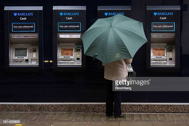 A customer shelters beneath an umbrella as she uses an automated teller machine outside a Barclays Plc bank branch in London UK on Monday Feb 11 2013...