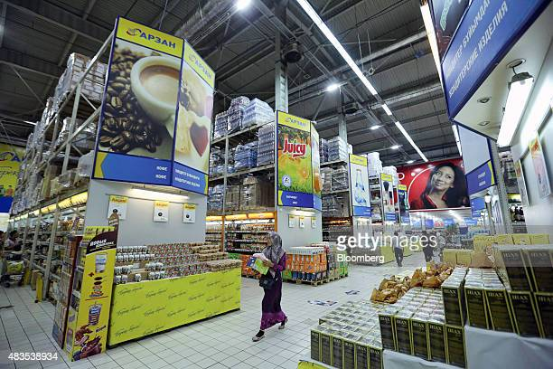 Customer shop for goods in the food aisles of an Arzan wholesale supermarket store in Almaty Kazakhstan on Friday June 26 2015 Kazakhstan's central...