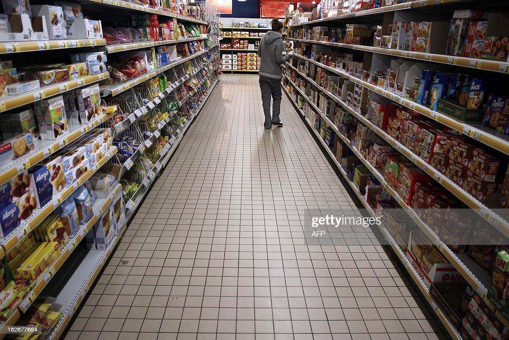 A customer shops at a supermarket in Herouville Saint-Clair, northwestern France, on February 26, 2013. AFP PHOTO/CHARLY TRIBALLEAU.