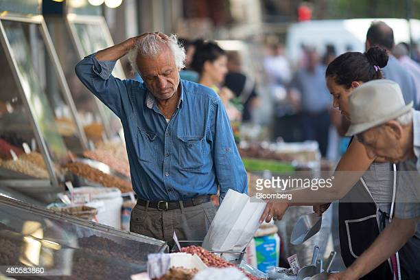 A customer shops for fresh olives at a market stall in Athens Greece on Monday July 13 2015 Greece has been in financial limbo since the government...