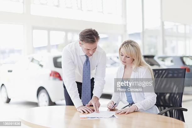 Customer signing at car dealership