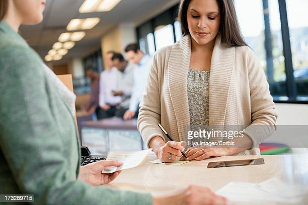 Customer signing bank receipt
