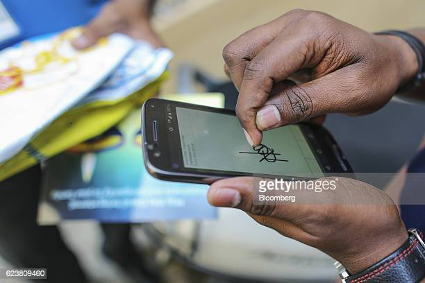 A customer signs an esignature on a smartphone on receiving a package from Flipkart Online Services Pvt's Ekart Logistics service in Bengaluru India...