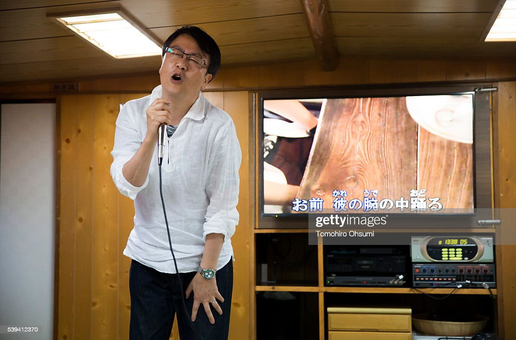A customer sings a song using a karaoke machine on a yakatabune, or traditional low barge style boat, operated by Mikawaya shipping agent, as it sails through Tokyo Bay on June 11, 2016 in Tokyo, Japan. About 35 companies operate over 100 yakatabune boats in Tokyo offering services such as dinner or karaoke inside the boats while cruising in Tokyo's bay area, according to the Tokyo Yakatabune Association.