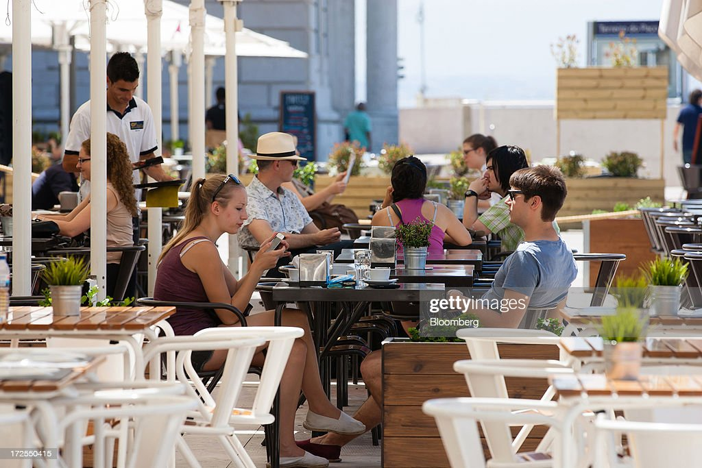 Customer sit at tables on an outdoor cafe terrace in Lisbon, Portugal, on Wednesday, July 3, 2013. Portuguese borrowing costs topped 8 percent for the first time this year after two ministers quit, signaling the government will struggle to implement further budget cuts as its bailout program enters its final 12 months. Photographer: Mario Proenca/Bloomberg via Getty Images