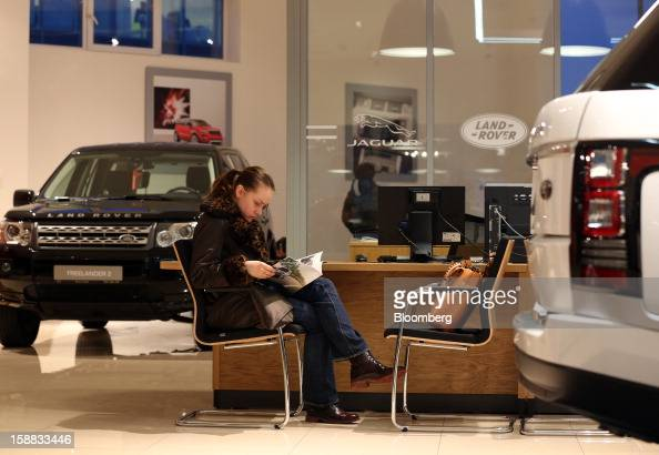 A customer sits and browses an automobile brochure inside a Jaguar Land Rover auto dealership in Moscow Russia on Thursday Dec 27 2012 Tata Motors...