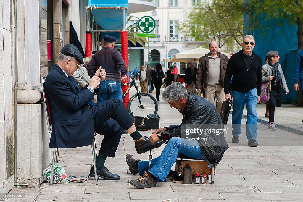 A customer sits and checks his mobile phone while his shoes are cleaned by a shoe cleaner on Rossio plaza in Lisbon, Portugal, on Monday, April 8, 2013. Portugal will carry out more spending cuts this year after the Constitutional Court blocked a plan to suspend a monthly salary payment to state workers and pensioners. Photographer: Mario Proenca/Bloomberg via Getty Images
