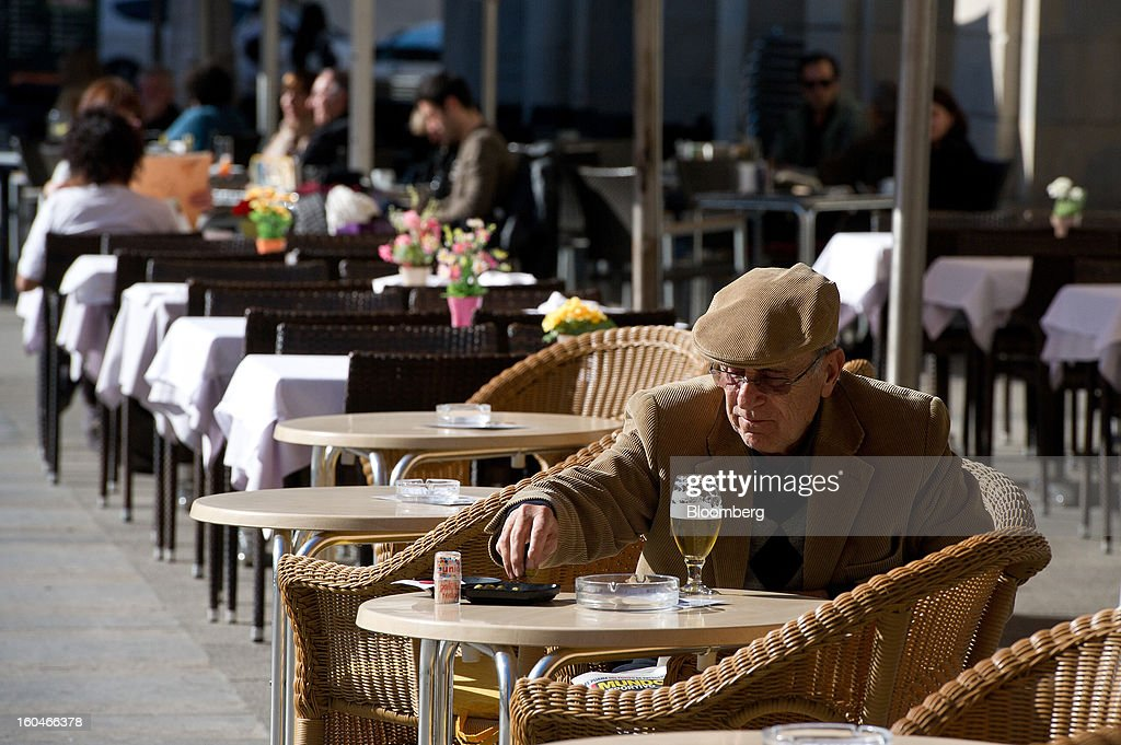 A customer sits and drinks a beer on the terrace of an outdoor cafe in Girona, Spain, on Thursday, Jan. 31, 2013. Spain's recession deepened more than economists forecast in the fourth quarter as the government's struggle to rein in the euro region's second-largest budget deficit weighed on domestic demand. Photographer: David Ramos/Bloomberg via Getty Images
