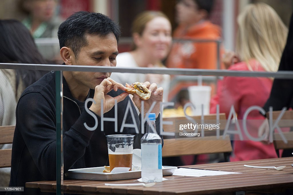A customer sits and eats a cheeseburger outside Shake Shack's new burger restaurant in London, U.K., on Tuesday, July 2, 2013. Shake Shack, opening in London's Covent Garden this week, started as a hotdog cart in New York's Madison Square Park, and has outlets in six U.S. states as well as in the Middle East and Turkey. Photographer: Simon Dawson/Bloomberg via Getty Images