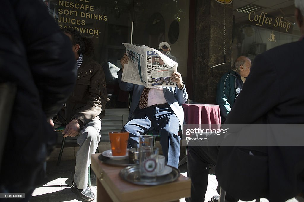A customer sits and reads a newspaper on the outdoor terrace of a cafe in Nicosia, Cyprus, on Monday, March 25, 2013. In a replay of tensions over aid for Greece at the outset of the crisis, European governments had wrangled over aid for Cyprus for nine months, exposing holes in the revamped economic management system that was built in three years of emergency policymaking, often at all-night summits. Photographer: Photographer: Simon Dawson/Bloomberg via Getty Images