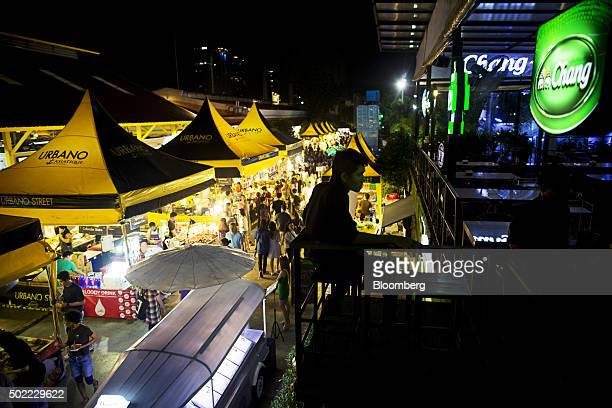 A customer sits at a bar overlooking food stalls at Asiatique The Riverfront openair mall in Bangkok Thailand on Friday Dec 18 2015 Thai economic...