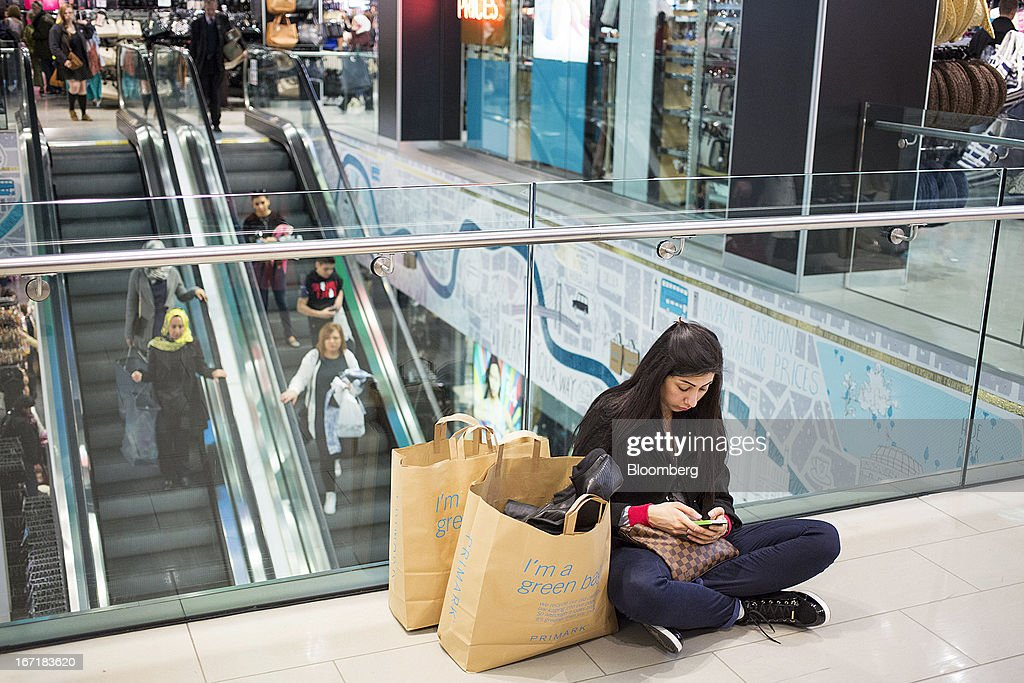 A customer sits besides her shopping bags while using a mobile device inside a Primark store on Oxford Street in central London, U.K., on Monday, April 22, 2013. Associated British Foods Plc, the owner of the Primark discount-clothing chain, fell the most in three months after Credit Suisse Group AG said it's unlikely the chain's profit growth can continue at the first half's pace. Photographer: Jason Alden/Bloomberg via Getty Images