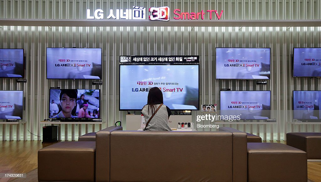 A customer sits in front of LG Electronics Inc. 3-D Smart televisions at one of the company's bestshop stores in the Gangnam area of Seoul, South Korea, on Wednesday, July 24, 2013. LG Electronics, the worlds second-largest television maker, posted second-quarter profit that missed analyst estimates on slowing demand for sets and increased spending on marketing for smartphones. Photographer: Woohae Cho/Bloomberg via Getty Images