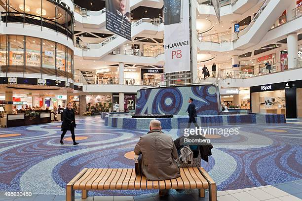 A customer sits on a bench in the atrium of the Blue City shopping mall near an advertisment center for a Huawei Technologies Co P8 smartphone in...