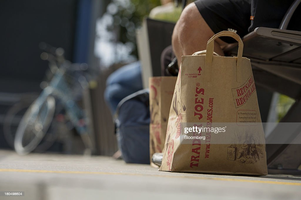 A customer sits on a bench next to shopping bags outside of a Trader Joe's Co. store in San Francisco, California, U.S., on Friday, Sept. 13, 2013. Trader Joe's Co., the closely held grocery store chain, will end health benefits for part-time workers next year, directing them instead to anew insurance marketplaces as companies revamp medical coverage to fit the U.S. Affordable Care Act. Photographer: David Paul Morris/Bloomberg via Getty Images