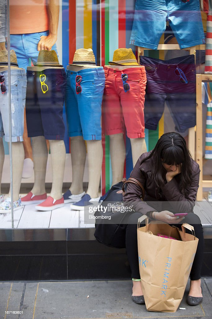 A customer sits with her shopping bag outside the window a Primark store on Oxford Street in central London, U.K., on Monday, April 22, 2013. Associated British Foods Plc, the owner of the Primark discount-clothing chain, fell the most in three months after Credit Suisse Group AG said it's unlikely the chain's profit growth can continue at the first half's pace. Photographer: Jason Alden/Bloomberg via Getty Images