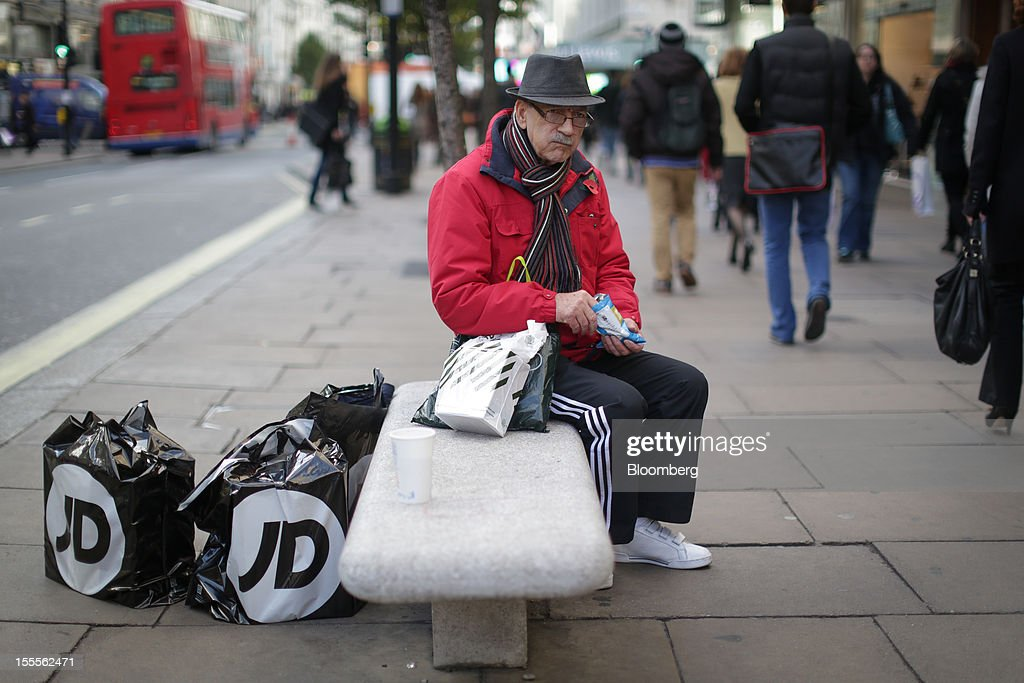 A customer sits with his JD Sports Fashion Plc and John Lewis Plc-branded shopping bags on Oxford Street in central London, U.K., on Monday, Nov. 5, 2012. Britain exited a double-dip recession in the third quarter with the strongest growth in five years as Olympic ticket sales and a surge in services helped boost the rebound. Photographer: Jason Alden/Bloomberg via Getty Images