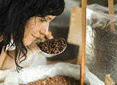 Customer smelling scoop of coffee beans in grocery store