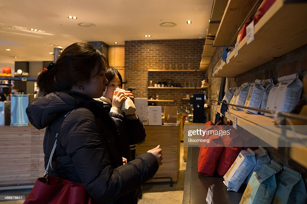 A customer smells a bag of roasted coffee beans at the Terarosa Coffee shop in Seoul, South Korea, on Tuesday, Feb. 4, 2014. South Korea is Asias fastest-growing market for arabica coffee, the mild-tasting beans used in premium blends. Photographer: SeongJoon Cho/Bloomberg via Getty Images