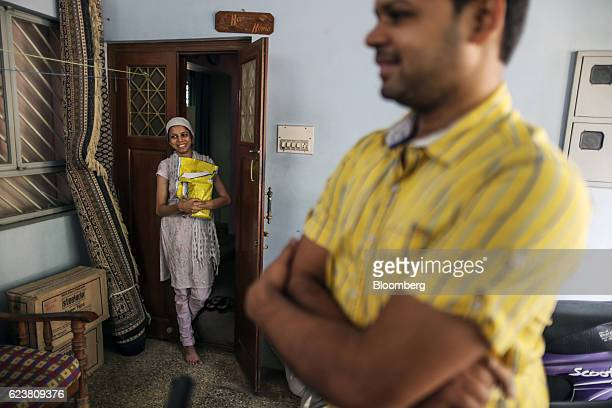 A customer smiles as she takes delivery of a package delivered by Flipkart Online Services Pvt's Ekart Logistics service at a home in Bengaluru India...