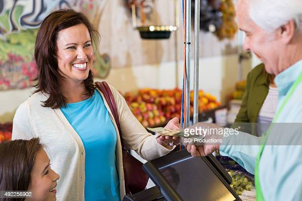 Customer smiling while paying for groceries in market