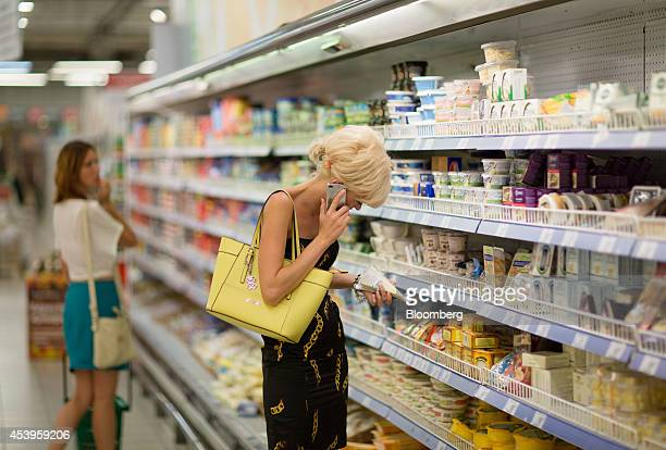 A customer speaks on a smartphone while choosing from a cabinet of imported cheeses inside an X5 Retail Group NV's Perekrestok hypermarket in Moscow...