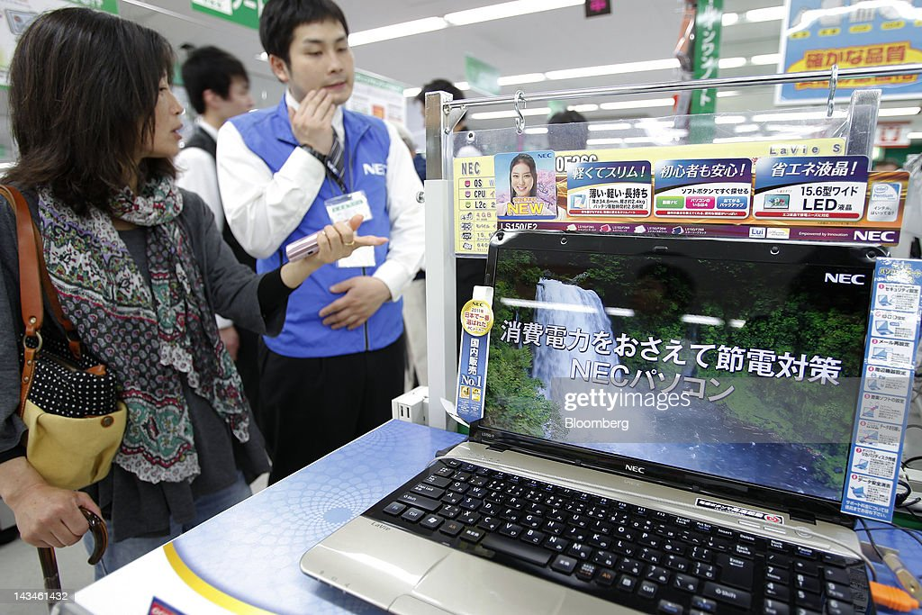 A customer speaks to a salesclerk near a NEC Corp. LaVie laptop computer at the Labi Ofuna electronics store, operated by Yamada Denki Co., in Yokohama City, Kanagawa Prefecture, Japan, on Friday, April 27, 2012. Consumer prices excluding fresh food rose 0.2 percent from the year before, exceeding estimates, a government report showed earlier today. Photographer: Kiyoshi Ota/Bloomberg via Getty Images