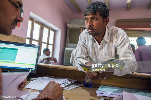 A customer speaks with an employee inside a branch of Gramin Bank of Aryavat sponsored by Bank of India in the village of Khurana Uttar Pradesh India...