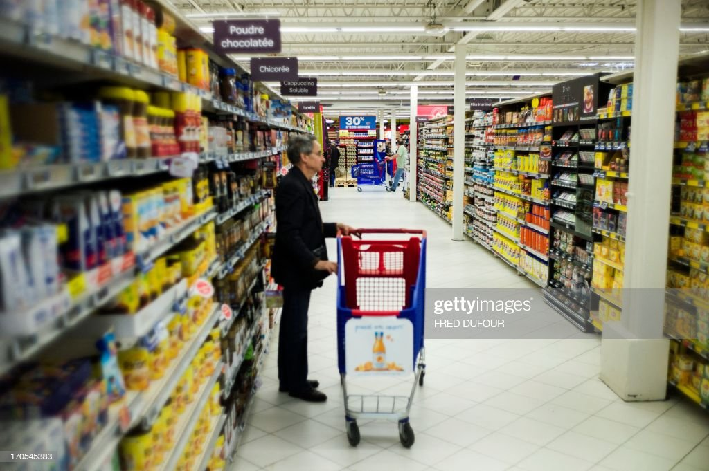 A customer stands beside his shopping cart in a Carrefour supermarket, on June 14, 2013 in Sainte-Geneviève-des-Bois, outside Paris. Installed in Sainte-Geneviève-des-Bois since fifty years, on June 15, 1963, this supermarket is the first of French giant retailer Carrefour group, but also the first in France. AFP PHOTO / FRED DUFOUR