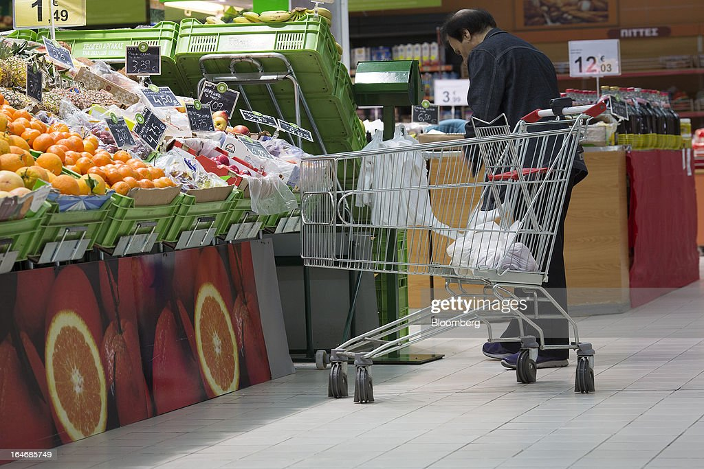 A customer stands besides an empty shopping cart in the fruit and vegetable department inside a Carrefour SA supermarket at the Mall of Cyprus in Nicosia, Cyprus, on Tuesday, March 26, 2013. Controls on capital movements to prevent money from draining out of the banking system -- allowed in exceptional circumstances under European Union law -- will remain for 'a matter of weeks,' Cypriot Finance Minister Michael Sarris said. Photographer: Simon Dawson/Bloomberg via Getty Images
