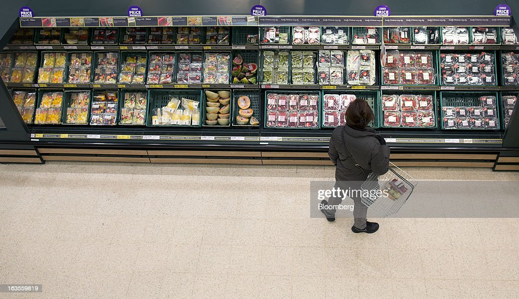 A customer stands by a selection of fresh fruit on display at a Tesco Plc supermarket in the borough of Kensington in London, U.K., on Tuesday, March 12, 2013. Tesco Plc, the U.K.'s largest grocer launched a 'Price Promise', its latest initiative offering to match the price of customers' purchases to that of it's rivals, including Wal-Mart Stores Inc.'s ASDA. Photographer: Simon Dawson/Bloomberg via Getty Images