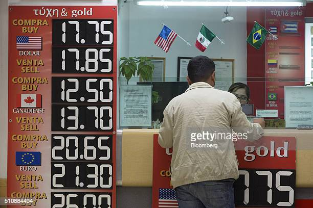 A customer stands in an exchange currency store as exchange rates for the US dollar the Canadian dollar and the euro are displayed in Mexico City...