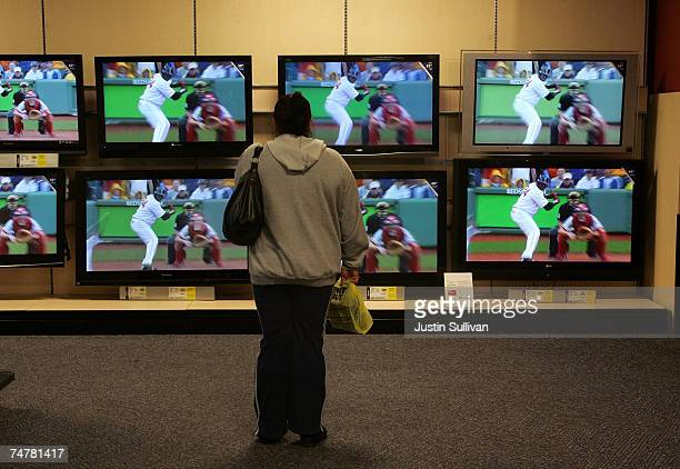 A customer stands in front of a wall of flat panel televisions at a Best Buy store June 19 2007 in San Francisco California Consumer electronics...
