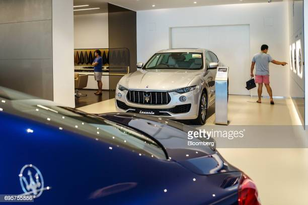 A customer stands next to a Maserati Levante vehicle at a Maserati SpA showroom in Singapore on Sunday June 4 2017 Singapores economy may be picking...