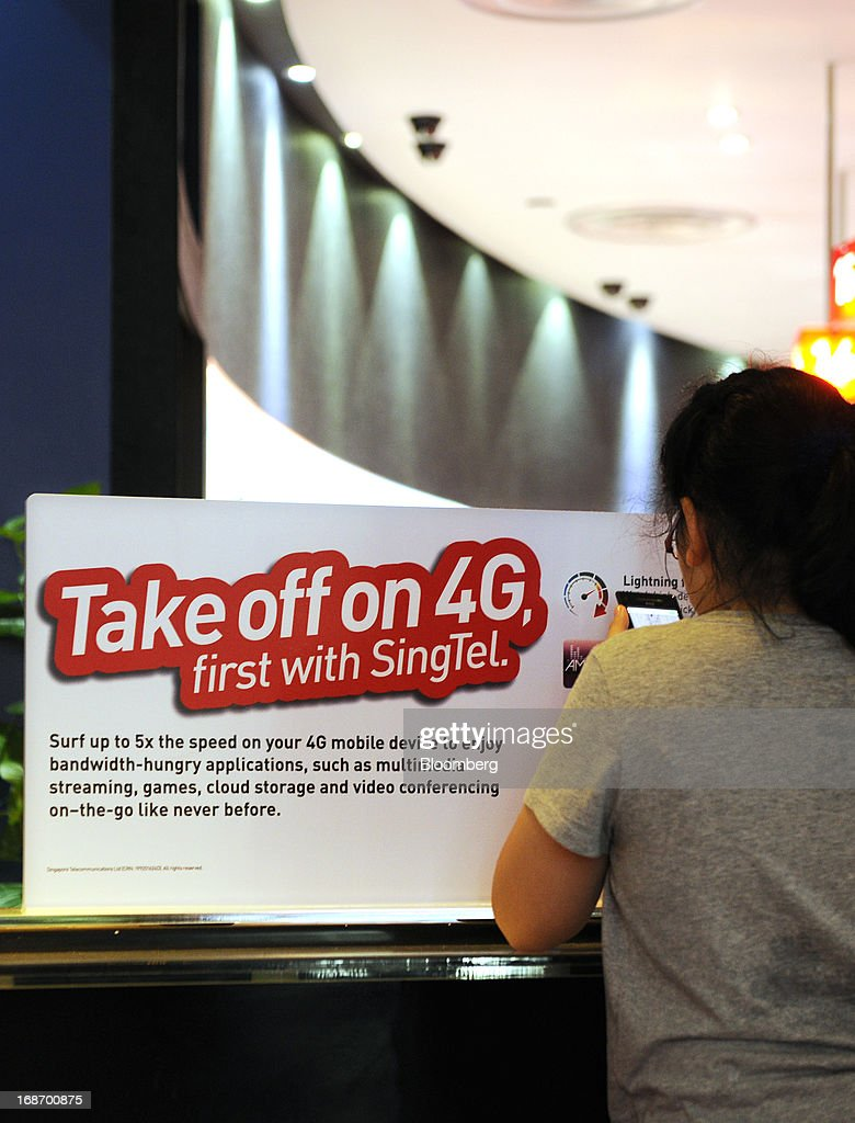 A customer stands next to an advertisement for Singapore Telecommunications Ltd.'s (SingTel) 4G network at a retail outlet in Singapore, on Monday, May 13, 2013. SingTel, southeast Asia's largest phone company, is scheduled to release fourth-quarter earnings on May 15. Photographer: Munshi Ahmed/Bloomberg via Getty Images