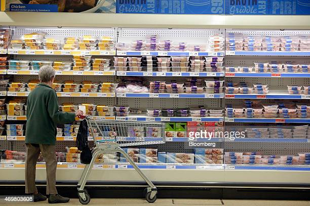 A customer stands with a shopping cart as she browses cuts of chicken displayed for sale in the fresh meat aisle inside a Sainsbury's supermarket...