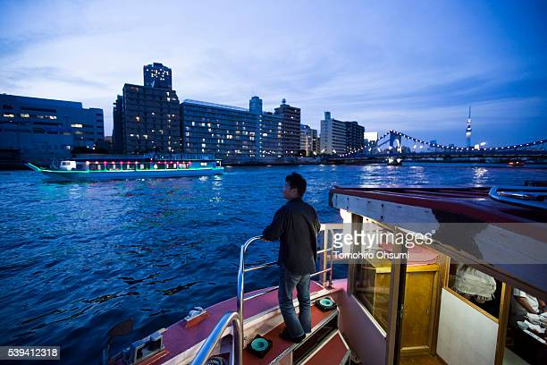 A customer stnds on the deck of a yakatabune or traditional low barge style boat operated by Mikawaya shipping agent sailing on the Sumida River at...